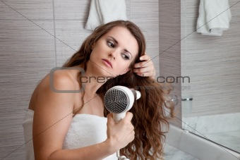 attractive woman using fen in bathroom