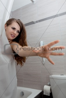 beautiful woman in bathroom streching for something
