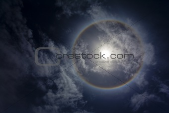Sun with circular rainbow and clouds