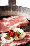 raw pork steak in a iron pan