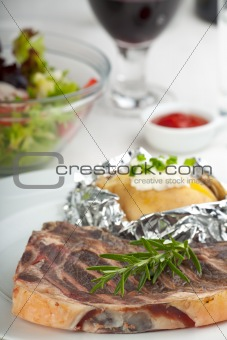 grilled steak and a rosemary leaf