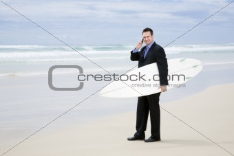 Business man in suit walking with surfboard on the beach