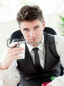 Portrait of confident businessman holing a cup od coffee in the