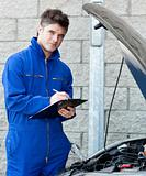 Attractive mechanic writing on a clipoard