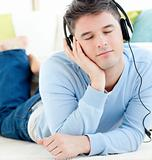 Relaxed man lying on the floor listening to music