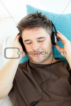 Attractive young man listening to music lying on a sofa