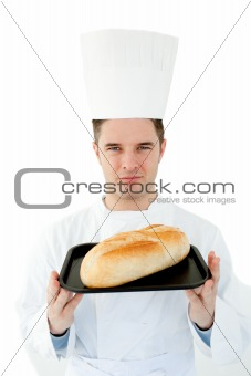 A male cook  holding  bread looking at the camera against white