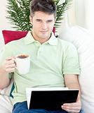 Smiling young man holding a cup of coffee looking at a laptop lying on a couch