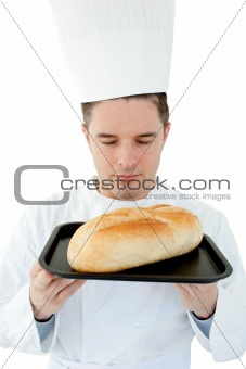 A male cook with closed eyes smell at  bread