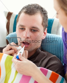 Attentive woman taking her sick husband's temperature on a sofa