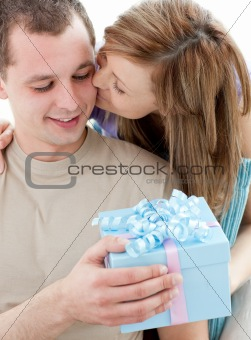 Beautiful girlfriend giving a present and a kiss to his handsome