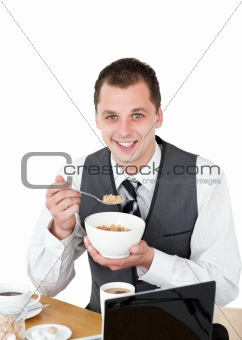 Smiling businessman eating cereals looking at the camera