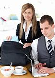 Businesswoman packing her bag businessman using laptop