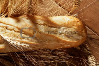 Bread over wooden table with wheat spikes