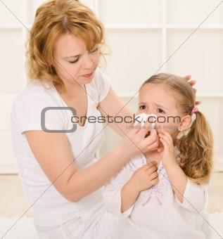 Woman blowing little girls nose