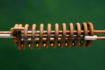 Aged mooring rusted spring on green water