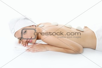 Beautiful woman relaxed on spa with stone treatment