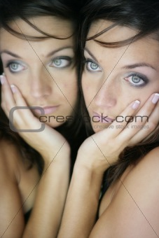Beautiful woman on the mirror as a twins portrait