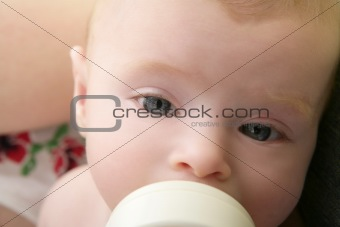 Baby blond little girl feeding drinking milk