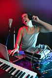 Dj with colorful light and music mixing equipment