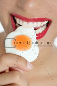 Beautiful woman mouth eating a jelly egg