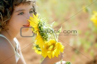 Beautiful little girl in a summer sunflower field