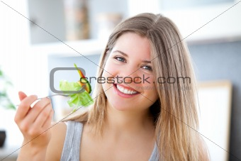 Cute woman eating a salad in the kitchen at home