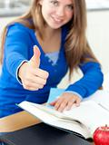 Motivated woman reading a book thumb up