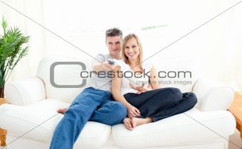 Adorable couple using a remote in the living-room