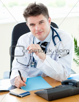 Portrait of an attractive male doctor sitting at his desk with a female patient with a pen