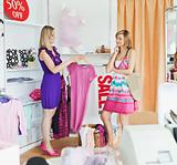 Radiant women choosing clothes together