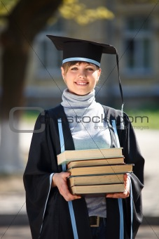Young female graduate with a stack of books