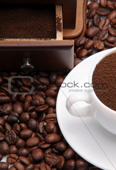 Fragment of a cup with ground coffee and coffee beens