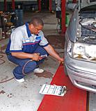 Auto Mechanic Performing Tire Pressure Inspection