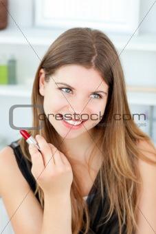 Beautiful girl using lipstick