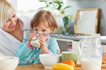 Blond mother and daughter having breakfast
