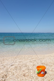 beautiful beach with child's bucket