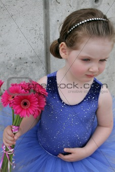 Little girl wearing ballet costume and holding flowers