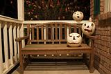White jack o'lanterns on a bench