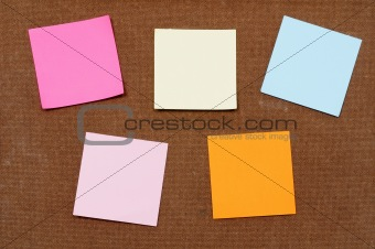 Multicolored post-it-notes sticks on wooden board.