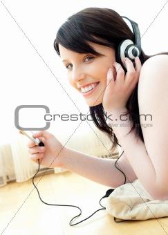 Positive caucasian teenager listen to music lying on the floor