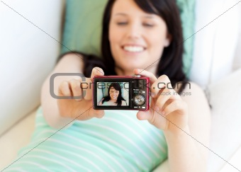 Attractive woman taking a picture of herself lying on bed