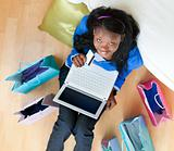 Cheerful afro-american teenager using a laptop sitting between shopping bags on the floor in the living room