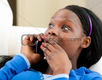 Astonished afro-american teenager talking on phone