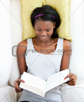 Bright female teenager reading a book lying on a sofa