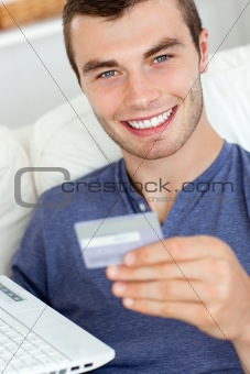 Animated young man holding a card and a latop sitting on the sofa at home