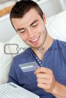 Attractive young man holding a card and a latop sitting on the s