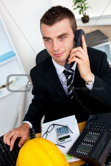 Caucasian young businessman talking on phone sitting at his desk