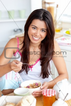 Smiling asian woman eating muesli with fruits