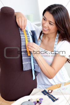 Bright asian woman working with clothes